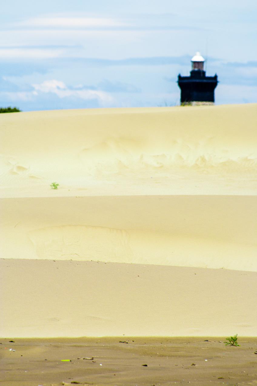 En la calima de Agosto, el faro se diluye entre las dunas. Extensa playa en la desembocadura del Ródano, Arles, Francia